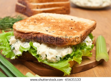 egg salad sandwich on brown toasted bread and ingredients - stock photo