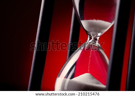 Egg timer or hourglass on a graduated red background in a conceptual image of passing time and time management - stock photo