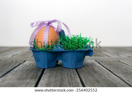 Egg with a ribbon in an egg carton as a easter nest on a wooden table. - stock photo