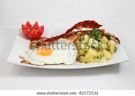 egg with meat and bacon and potato on white plate isolated on white background - stock photo