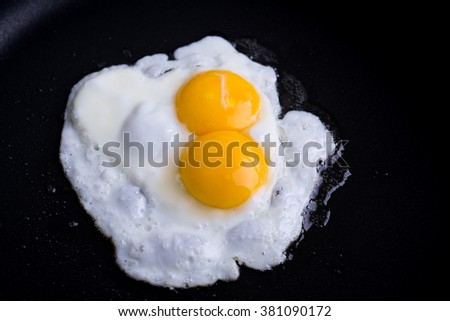 Egg with two yolks in pan - stock photo