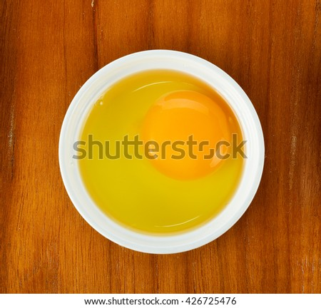 Egg yolk in the bowl on wooden background. - stock photo