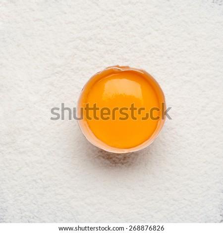 egg yolk on flour. Baking background. - stock photo