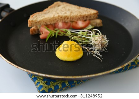 Egg yolk on hot skillet / non-stick pan / frying pan with green gram sprouts ,vegetable sandwitch, oil free cooking,break fast with less fat, whole wheat bread, kids snack,food art,bullseye egg recipe - stock photo