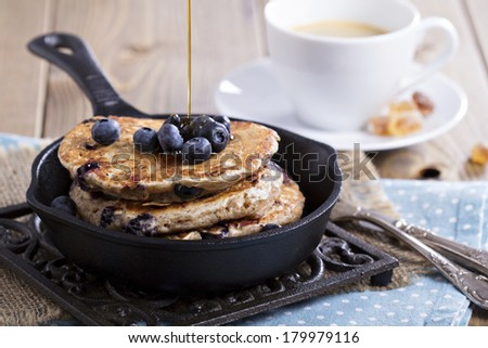 Eggless pancakes with banana and blueberries in a small pan - stock photo