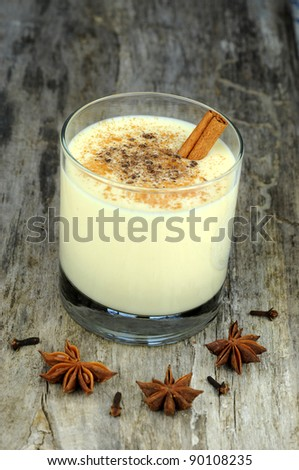Eggnog on rustic wooden background with anise seed, cinnamon and cloves - stock photo