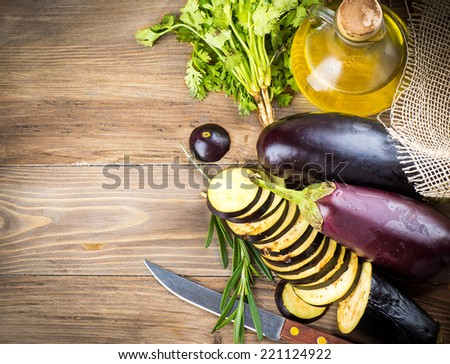 Eggplant and olive oil on a wooden board - stock photo