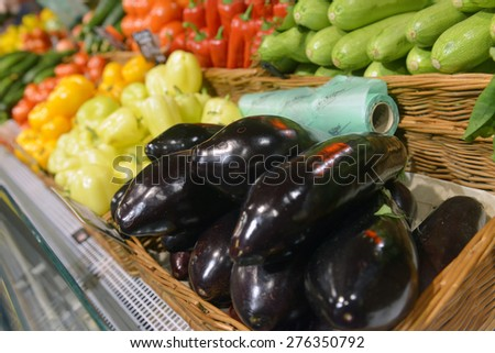 Eggplant and vegetables on display in supermarket - stock photo