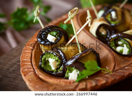 Eggplant rolls with pesto and feta on vintage wooden plate. Soft focus - stock photo