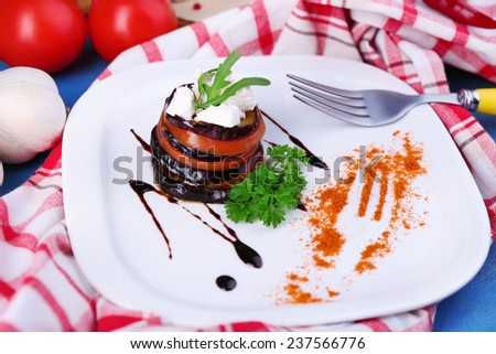 Eggplant salad with tomatoes and feta cheese on plate, on napkin,  on wooden background - stock photo