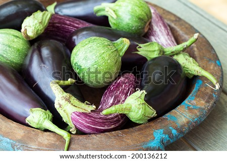 Eggplants and round zucchini on wooden plate - stock photo