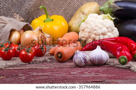 Eggplants, cauliflower, pepper, carrots, tomatoes, potatoes, onions and garlic on a wooden table