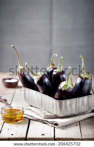 Eggplants in a vintage metal box on a wooden background - stock photo