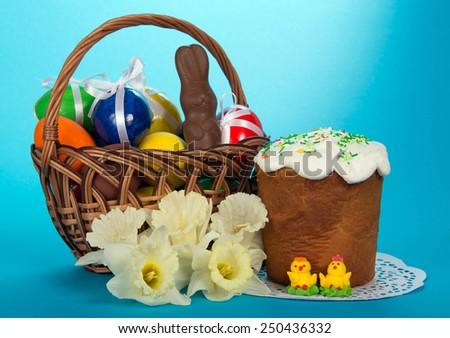 Eggs and a chocolate rabbit in a basket, an Easter cake, marzipan chickens and a bouquet of white narcissuses, on the blue - stock photo