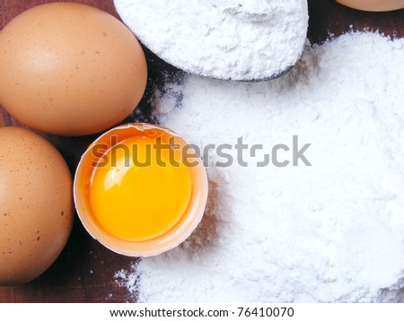 Eggs and flour on a wooden board - stock photo