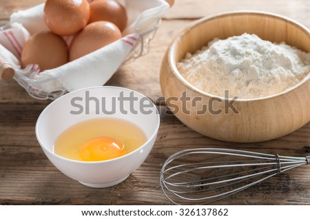 Eggs and flour on wood table. - stock photo