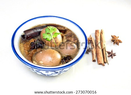 "Eggs and sweet pork with fried tofu,boiled in brown sauce(Thai food called ""Pa lo""), on white background - stock photo"