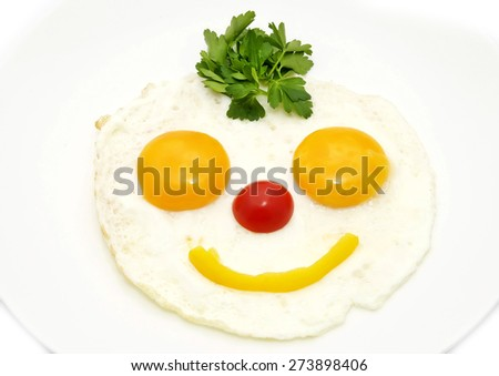 eggs as a smiley face adorned with greenery on a white plate - stock photo