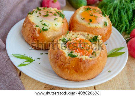 Eggs baked in a bun with ham, cheese and herbs. French breakfast. - stock photo