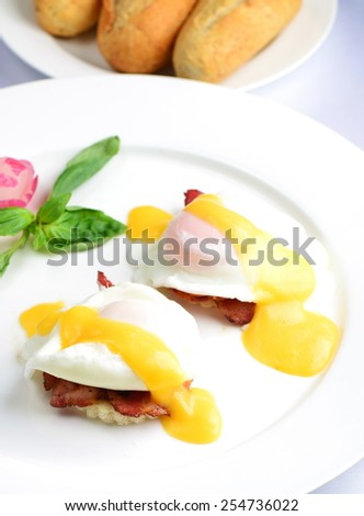 Eggs Benedict- toasted English muffins, ham, poached eggs, and delicious buttery hollandaise sauce - stock photo