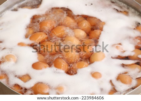 Eggs boiled with water in the big pot - stock photo