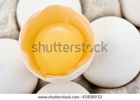 Eggs closeup with one egg is broken - stock photo