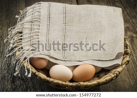 Eggs coated with a doily in basket on the boards