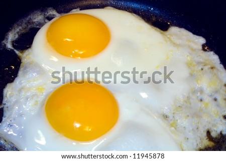 Eggs frying in open frying pan - stock photo