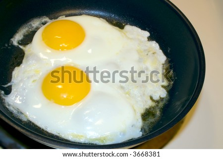 Eggs frying in pan on stove - stock photo