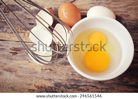 Eggs in a bowl with whisk - stock photo