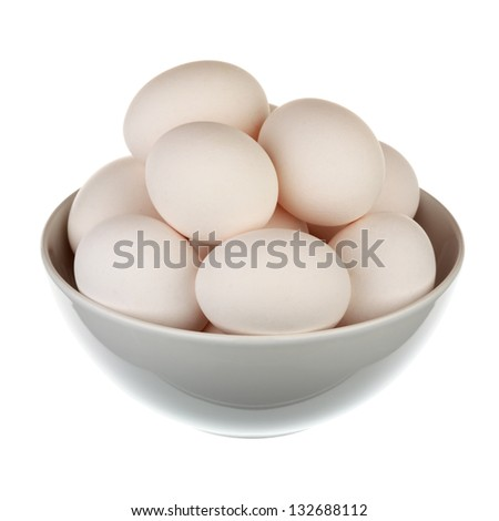 Eggs in a cup over white background - stock photo