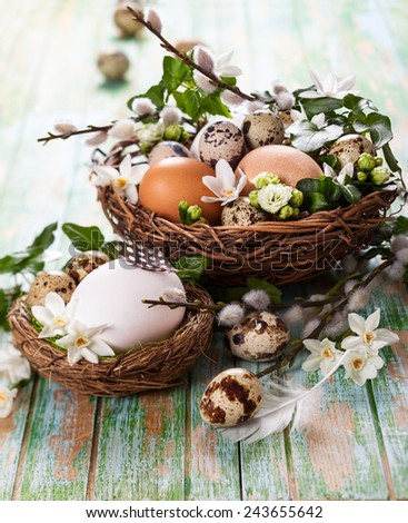 eggs in a nest with flowers,feathers on a wooden table - stock photo