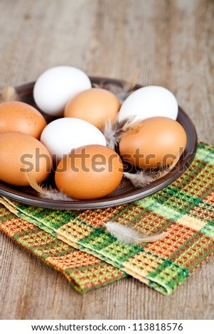 eggs in a plate, towel and feathers on rustic wooden table