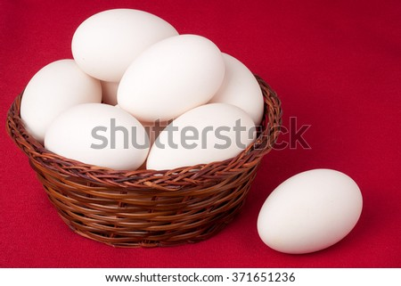 eggs in a wicker basket on a red background.