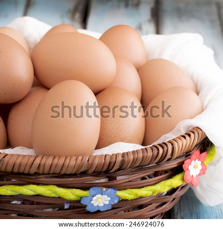 Eggs in basket isolated on wooden table - stock photo