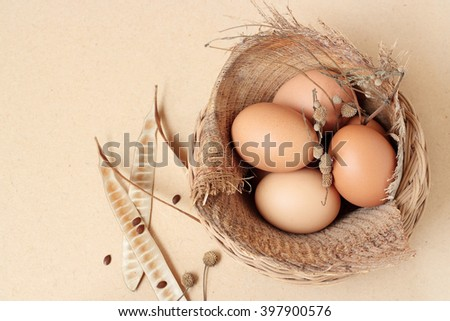 eggs in basket on wood table - stock photo