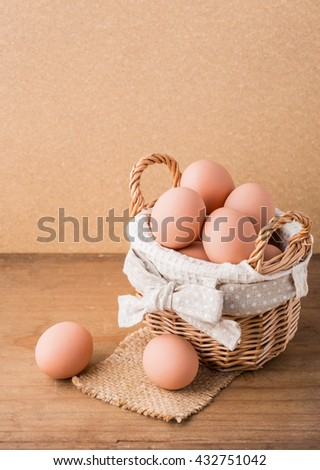 eggs in basket on wooden background - stock photo