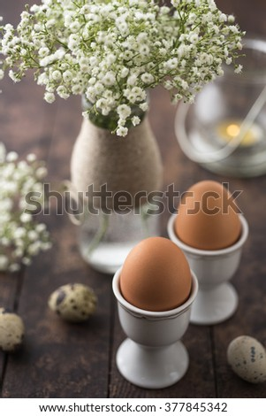Eggs in cups with flowers - stock photo