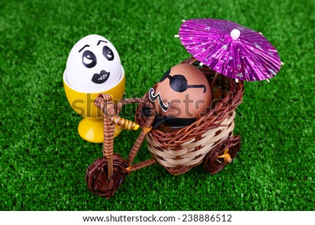 Eggs in egg cup and on bicycle on green background - stock photo