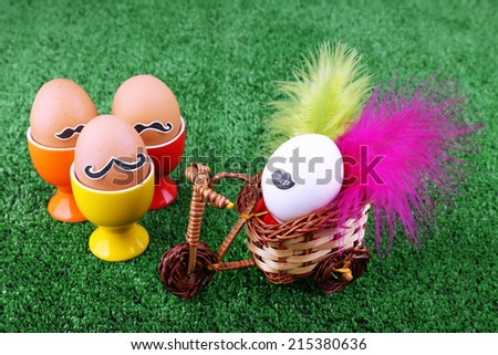 Eggs in egg cups and on bicycle on green background - stock photo