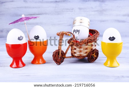 Eggs in egg cups and on bicycle on grey wooden background - stock photo