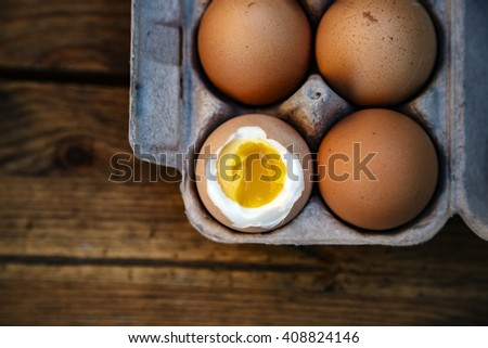 Eggs in paper tray. one soft-boiled. view from above - stock photo