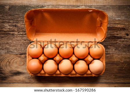 Eggs in the package on wooden table - stock photo