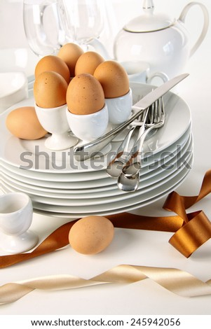 Eggs in white egg cups on a pile of plates with ribbons - stock photo