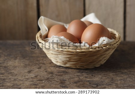 eggs in wicker basket on old wooden background - stock photo