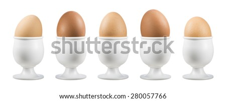 eggs on eggcup in a row on white background - stock photo