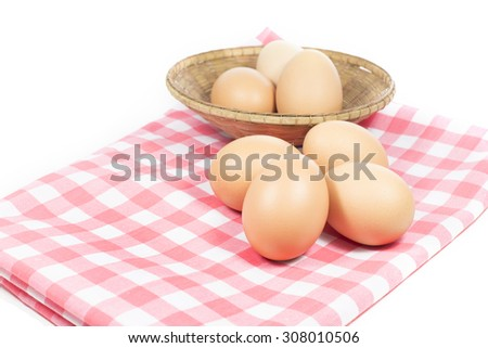Eggs on pink color plaid and basket on white background