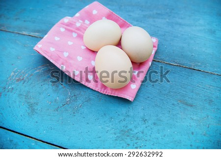Eggs on pink tablecloth over old blue wooden background. Top view - stock photo