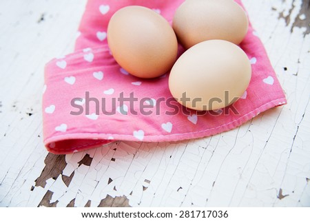 Eggs on pink tablecloth over vintage cracky white wooden background.  - stock photo