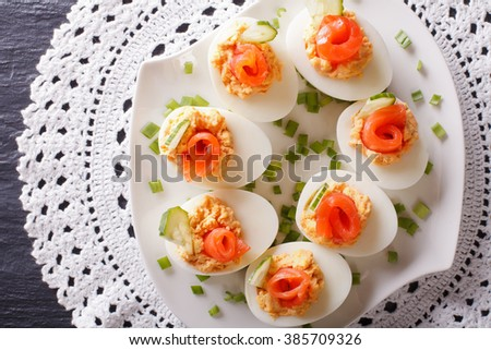Eggs stuffed with salmon, cheese and cucumber closeup on a table. Horizontal view from above